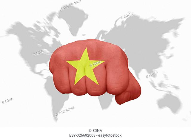 fist with the national flag of vietnam on a world map background