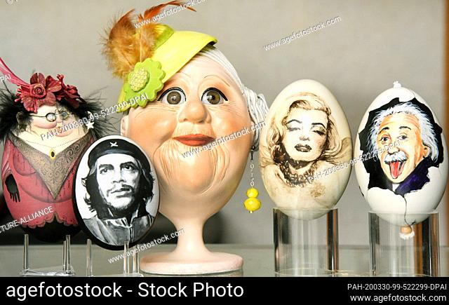 28 February 2021, Saxony, Leipzig: On a glass table of the collector and Easter egg artist Kerstin Dischereit there are (r-l) two goose eggs with the portraits...