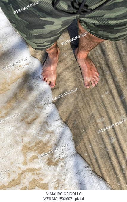 Feet of a man standing on a sandy beach enjoying the waves, Cahuita National Park, Costa Rica