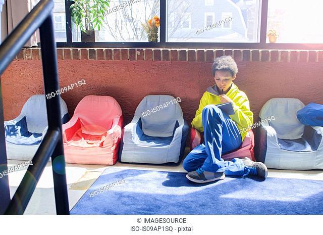 Boy sitting alone in classroom using digital tablet