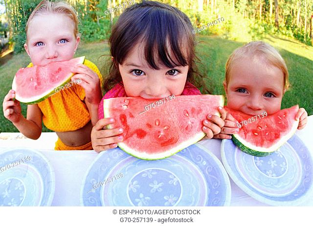 Three girls eating watermelon outdoors