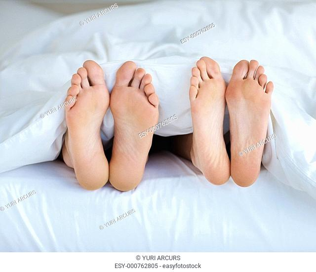 Closeup of a couple's feet in bed sleeping besides each other