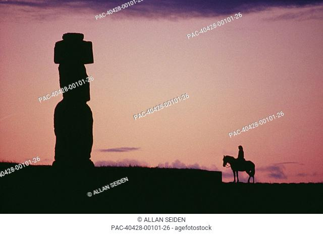 Easter Island, Silhouette of ancient stone statue and lone horseback rider against pink sunset sky