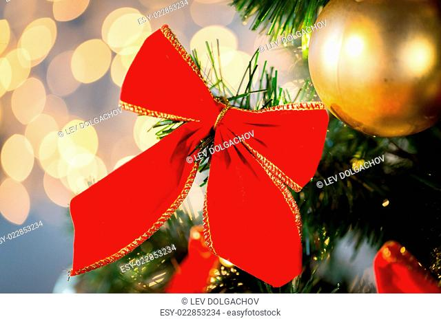 holidays, new year, decor and celebration concept - close up of christmas tree decorated with red bow and ball