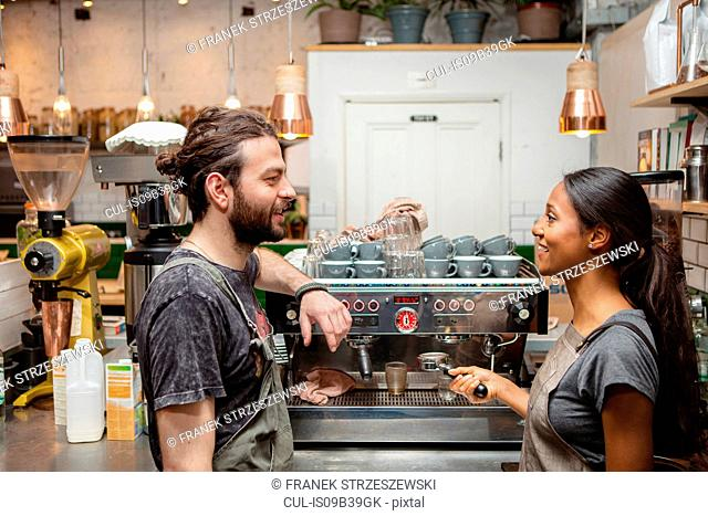 Male and female baristas talking by cafe coffee machine