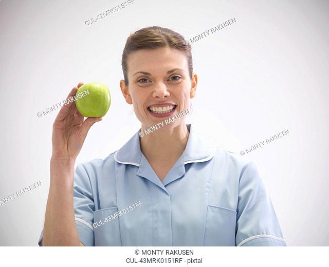 Smiling dentist holding apple