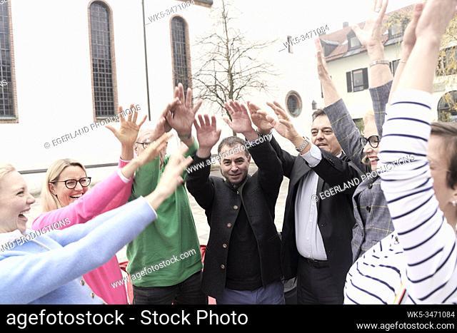 Group of friends raising hands together. Starnberg, Bavaria, Germany
