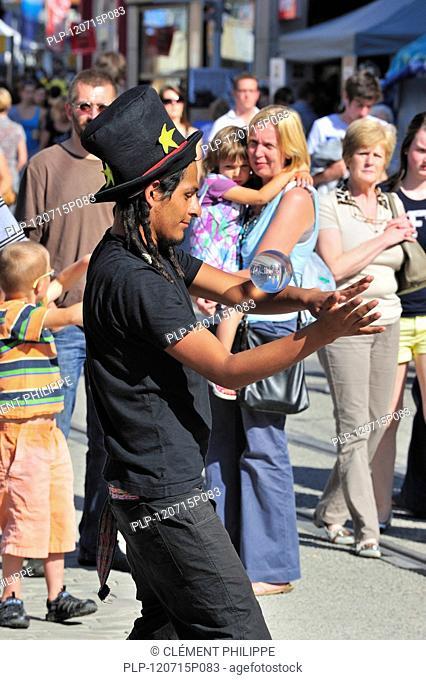 Black street performer balancing glass ball at the Gentse Feesten / Ghent Festivities in summer, Belgium