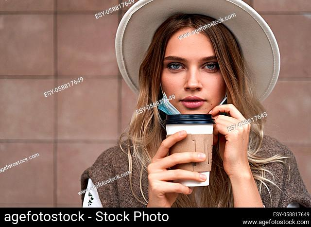 Beautiful vaccinated girl drinking coffee while pulling fown the protective face mask