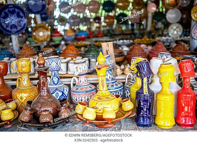 A close up of colorful Tajine pots and other pottery for sale at outdoor marketplace, Tangier, Morocco
