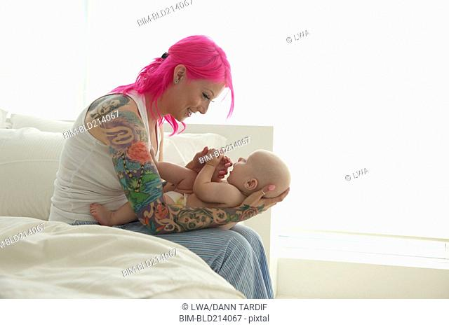 Caucasian mother with pink hair and tattoos cradling baby