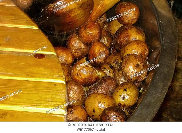 Fried potatoes with the peel. Potatoes fried in a pan on the bonfire. Potatoes with peel in pan in outdoor