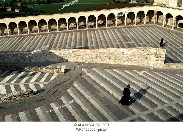 High angle view of two people walking in the courtyard of a basilica, Basilica Of San Francisco, Assisi, Umbria, Italy