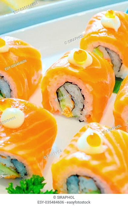Salmon roll sushi with salmon egg on top in white dish