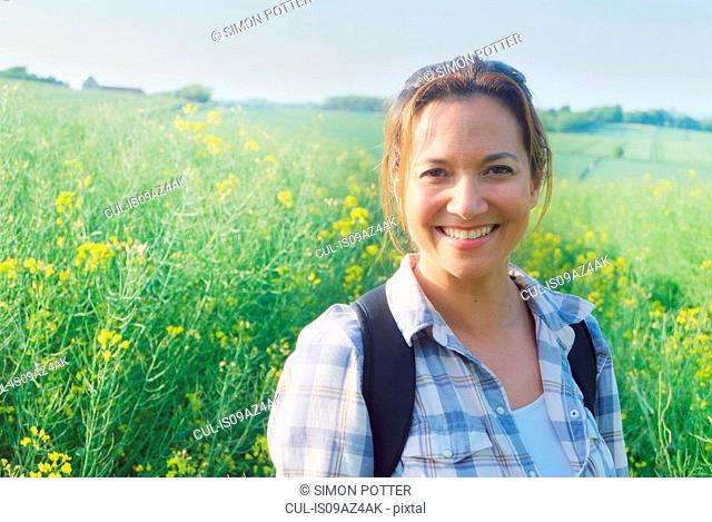 Portrait of woman in rapeseed field looking at camera smiling