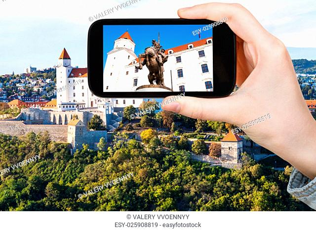 travel concept - tourist photos statue of King Svatopluk I in Bratislava Hrad castle on smartphone