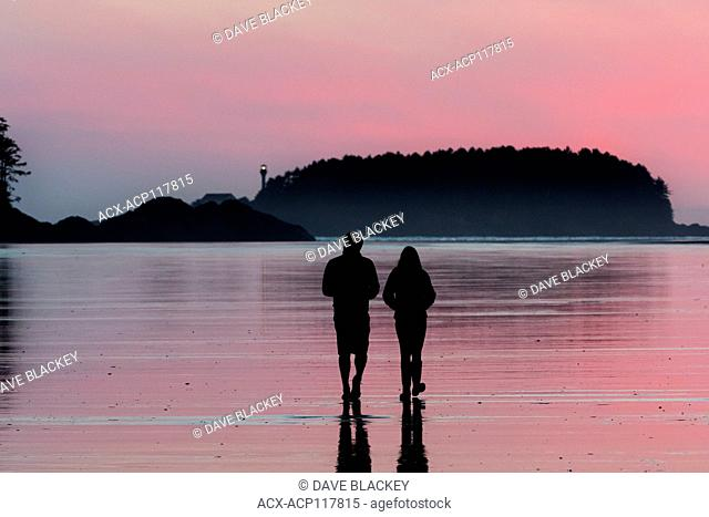 A young couple walks along Chesterman Beach near Tofino, British Columbia. Lennard Island Lighthouse is in the background