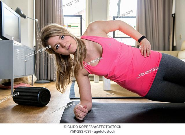 Tilburg, Netherlands. Young adult girly woman working out inside her living room