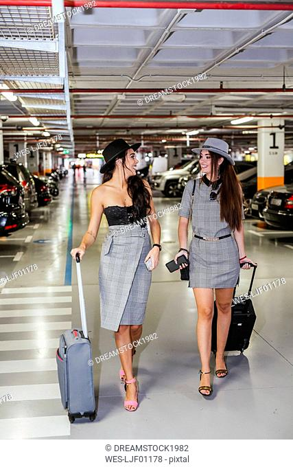 Two fashionable young women with baggage walking in airport car park