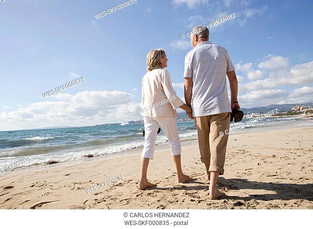 Spain, Mallorca, Senior couple walking along beach
