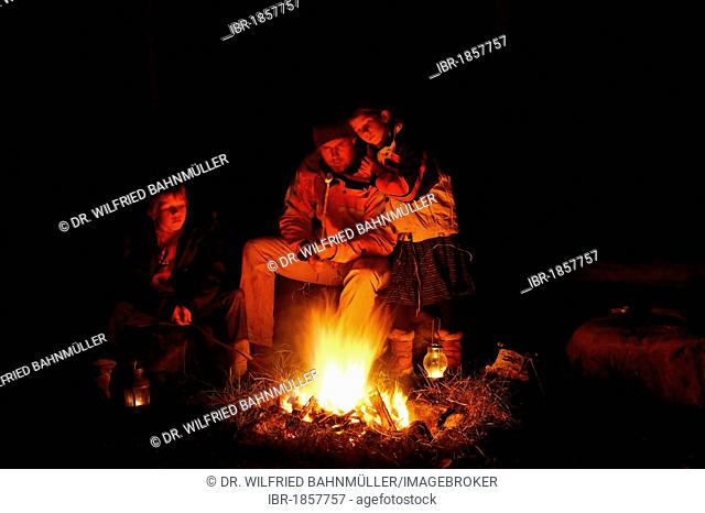 Father with his children sitting at a campfire
