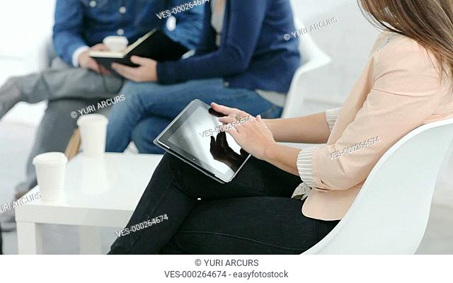 Beautiful young woman turning to smile at you while working comfortably on her touchpad