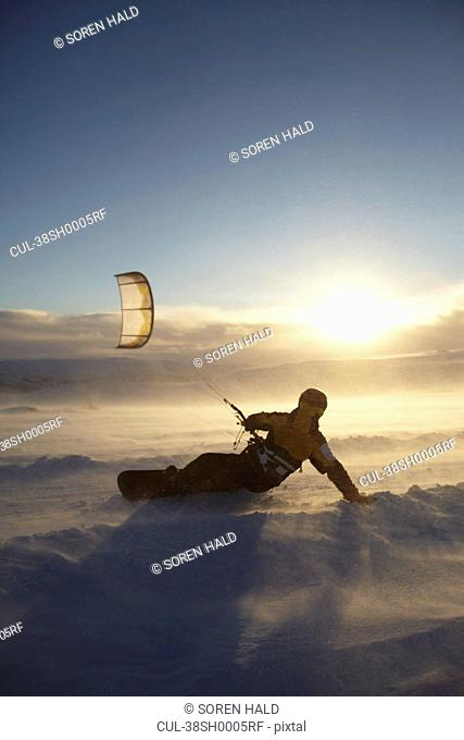 Man windsurfing on snowboard