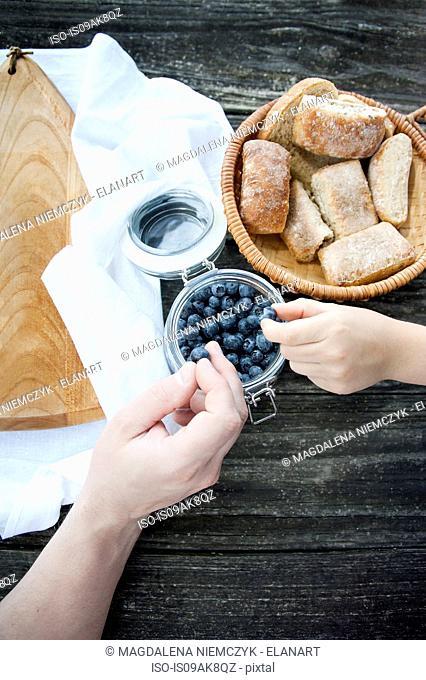 People taking blueberries from jar