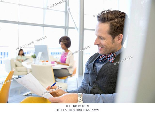 Smiling businessman with paperwork in office