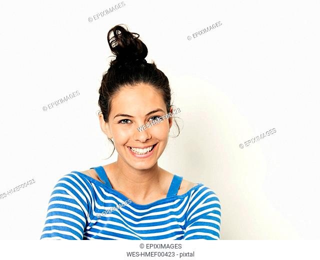 Beautiful young woman with black hair and blue white striped sweater is posing in front of white background