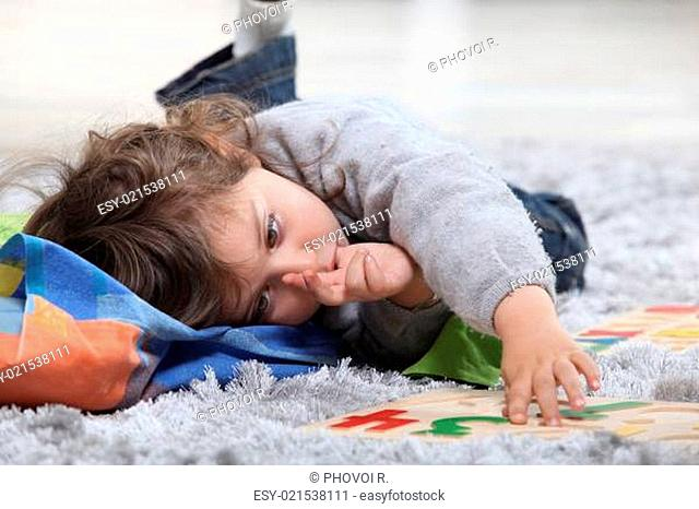 Child lying on the floor playing with a puzzle