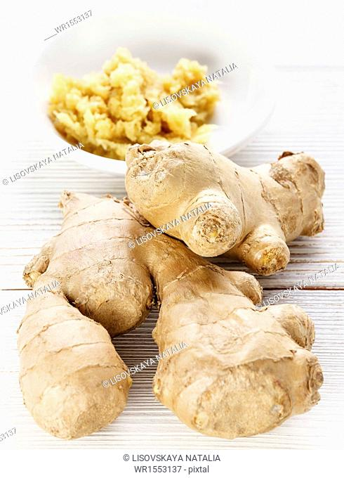 Raw ginger root spice on wooden table