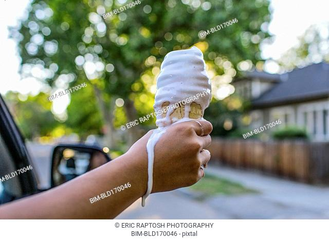 Close up of hand of Chinese girl holding melting ice cream cone