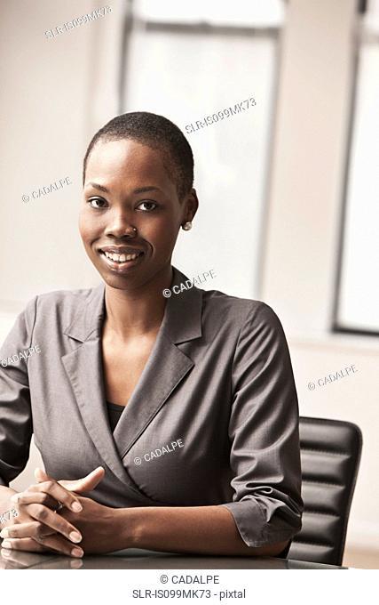 Young businesswoman at desk, portrait