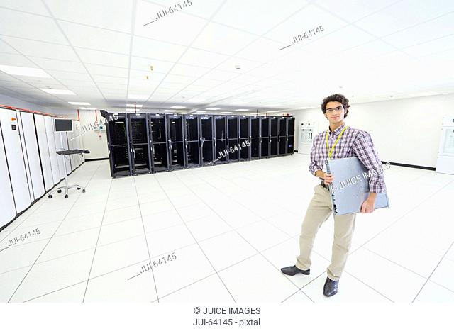 Technician, looking at camera, holding server drive in server room
