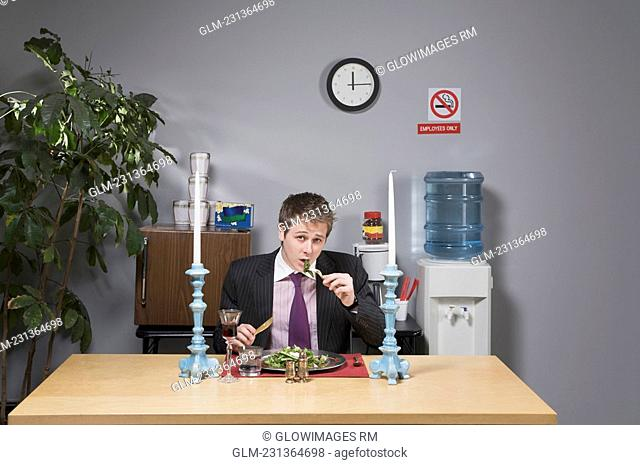 Portrait of a businessman having lunch in the office