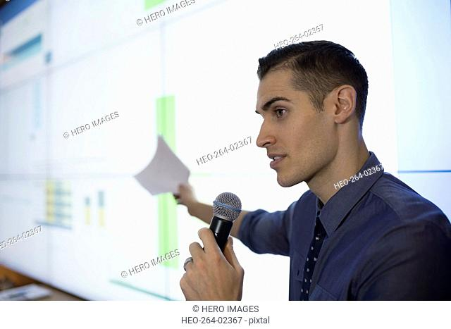 Businessman with microphone speaking at projection screen