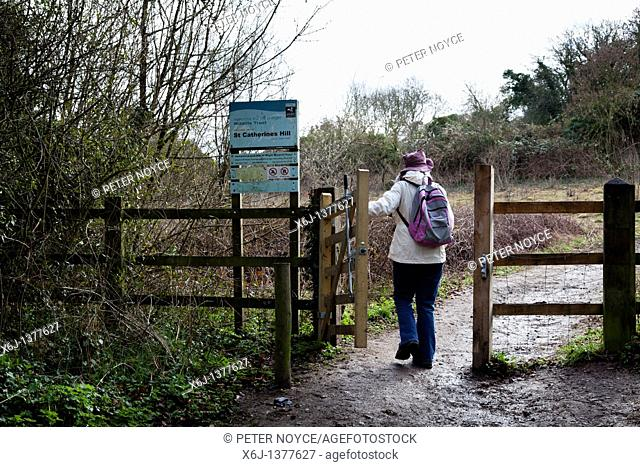 walker passing through gate to St Catherines Hill, Winchester UK