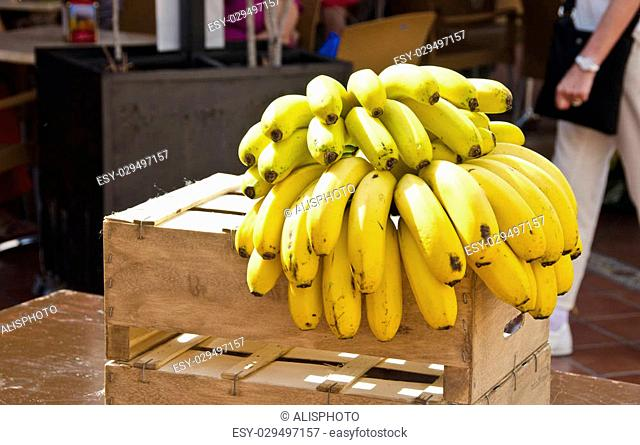 Cluster of yellow bananas on wooden box in the street with people walking by on sunny day