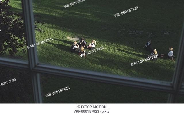 WS, View through a window of children in a schoolyard