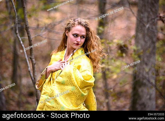 A 28 year old blond woman dressed in a yellow kimono in a forest setting