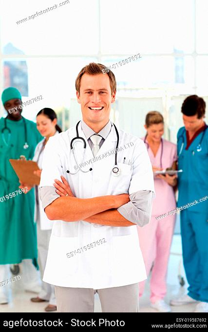 Young and smiling doctor with his team in the background