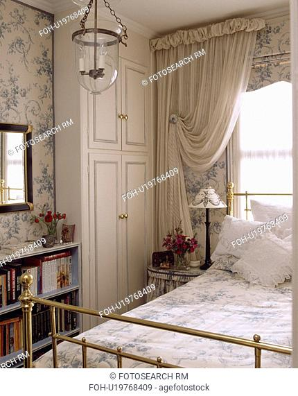White curtains and blue+white blind above brass bed in bedroom with fitted white wardrobe and blue floral wallpaper