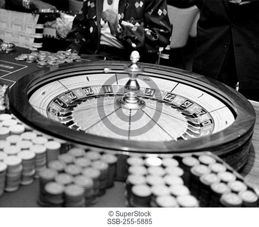 Close-up of roulette wheel with gambling chips in casino