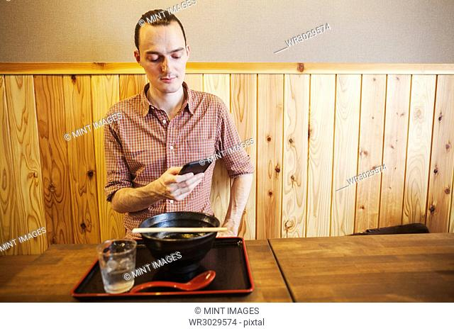 A western man in a noodle restaurant, using his smart phone. Tray and bowl, spoon and glass of water on the table