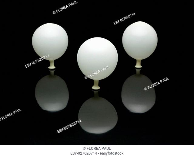 composition with three white balloons with black background