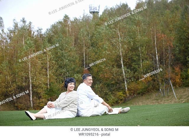 middle aged couple sitting on grass back to back