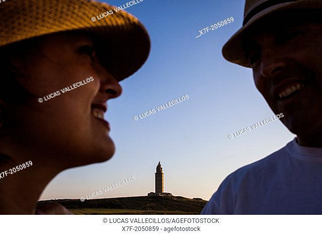 Couple in Punta Herminia gardens, in background Tower of Hercules, Roman lighthouse, Coruña city, Galicia, Spain