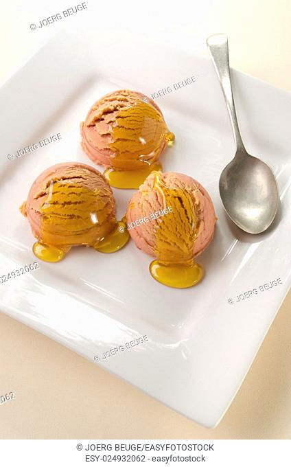 strawberry and apricot ice cream with acacia honey on a white plate