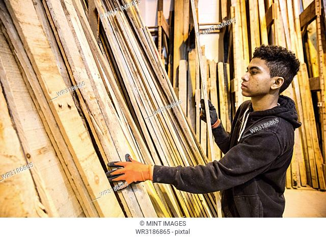 Young man wearing work gloves standing next to a stack of wooden planks in a warehouse
